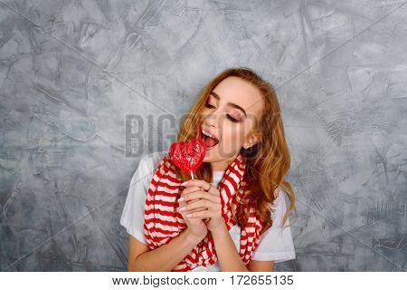 Young girl with candy near her face on the blue background