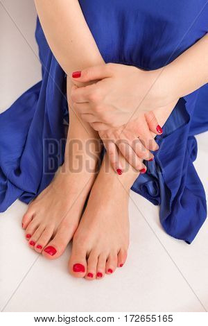 Young woman's hands and feet with red manicure and pedicure. A woman in a blue skirt sitting on a floor.