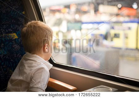 Cute little kid boy in a white t-shirt looking at the city out of the train window.  Child travelling by railway. young traveler.