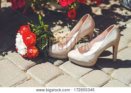 beautiful wedding shoes standing at street near bouquet with roses