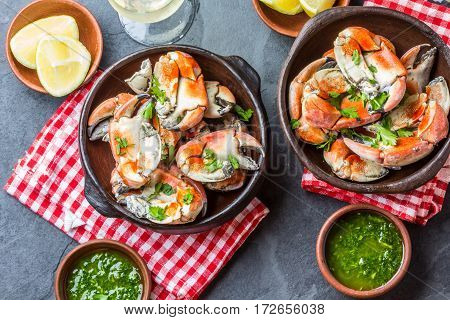 Seafood. Crabs tentacles on clay bowl with wite wine, lemon and herbs sauce on slate background. Top view