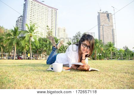 Girl enjoy reading a book laying on grass of park outdoor with coffee break