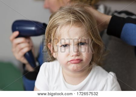 Little girl drying hair