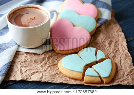 Heart shaped cookies with cup of coffee and parchment, closeup