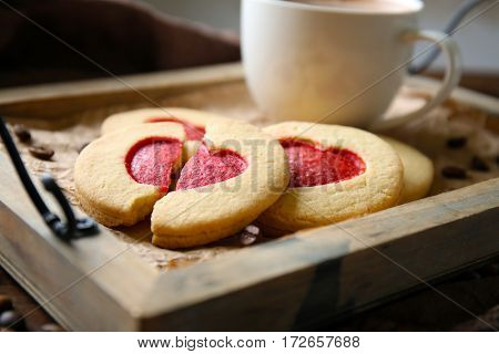 Cookies with coffee on wooden tray, closeup