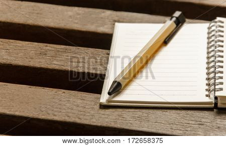 A blank notebook page and pen on wood table. Top view with copy space.