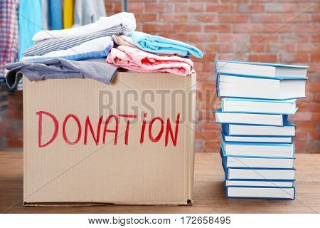 Donation box with clothes and books on table in the room