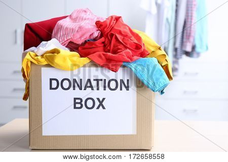 Donation box with clothes on table in the room