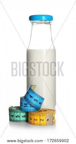 Milk diet concept. Bottle and measuring tapes isolated on white