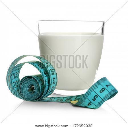 Milk diet concept. Glass and measuring tape isolated on white