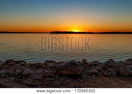 Sunset over a lake in Oklahoma with foreground of rocks.