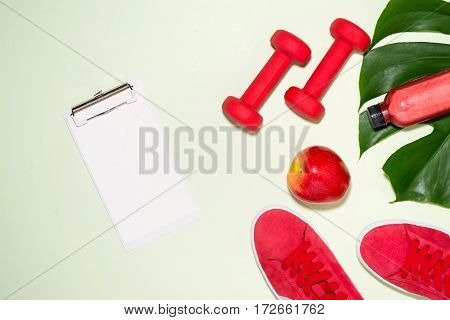 Fitness Concept. Sneakers, Apple, Dumbbell And Fruit Juice Bottle On Pastel Color Background.