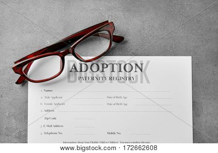 Glasses and adoption blank on table