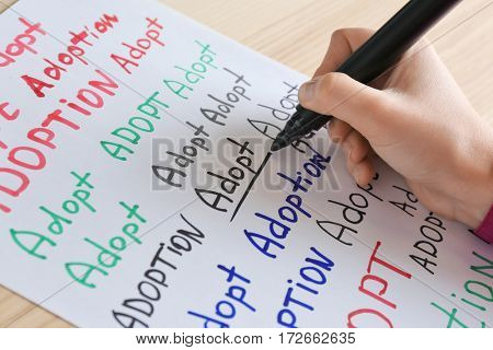 Female hand writing word