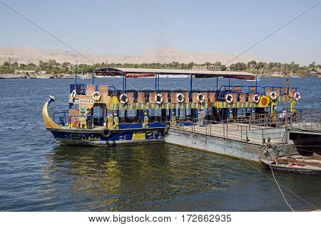 LUXOR EGYPT - FEBRUARY 9 2017: Crew resting at the pontoon for the public ferry which crosses the River Nile between Luxor and the West Bank on a sunny day in mid winter.