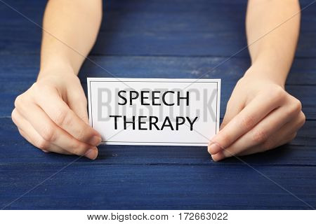 Speech therapy concept. Hands holding card on blue wooden background