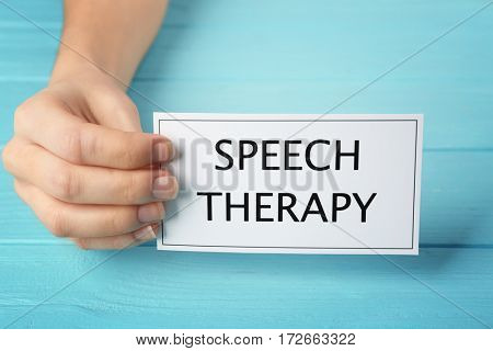 Speech therapy concept. Hand holding card on blue wooden background