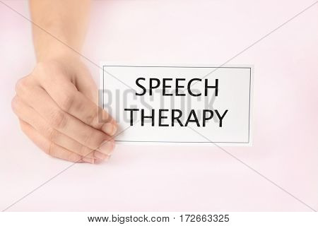Speech therapy concept. Hand holding card on light background