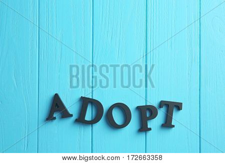 Word ADOPT made of letters on wooden background. Child custody concept