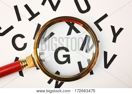 Magnifier and letters on light background, closeup
