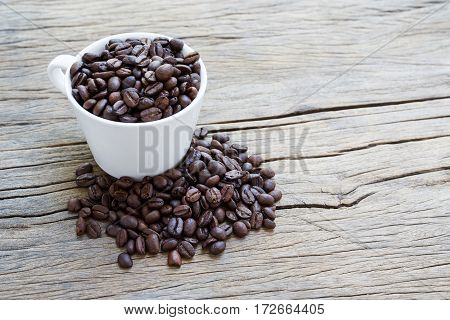 Cup coffee and coffee beans on wooden background