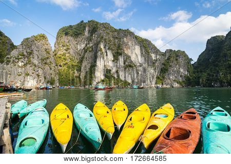 Colourful kayaks with limestone mountains background at Halong bay Vietnam
