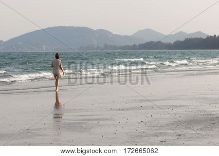 Senior woman walking on the shore of the storm sea.