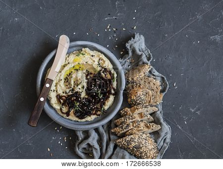 Balsamic caramelized onion hummus and whole wheat multi seed baguette on a dark background. Delicious vegetarian snack