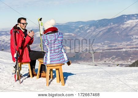 A couple is resting on lounges in picnic zone on european ski resort.