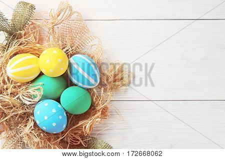 Easter Eggs In The Nest On White Wooden Background