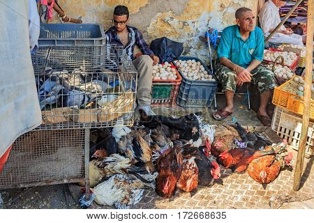 Fes Morocco - May 11 2013: Male vendors selling live chicken pigeons and eggs at a Moroccan souk Moroccan market in the medina