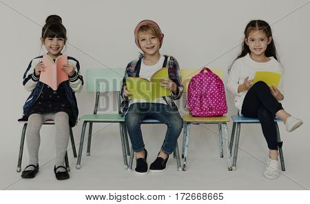 Group of Students Reading Book Sitting on the Chair