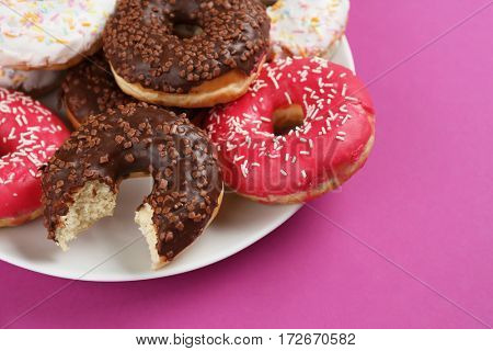 Tasty glazed donuts on color background