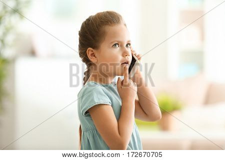 Cute little girl talking by mobile phone at home