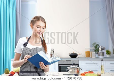 Young woman with recipe book at kitchen