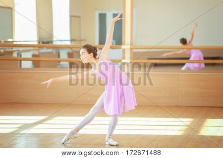 Young beautiful ballerina training in dance hall