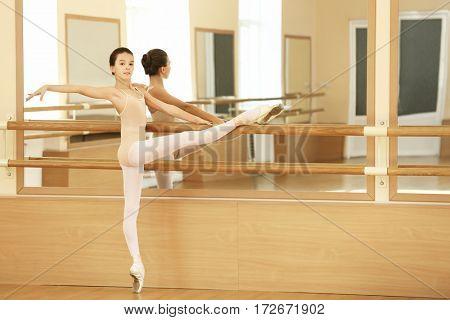 Little ballerina training in dance hall
