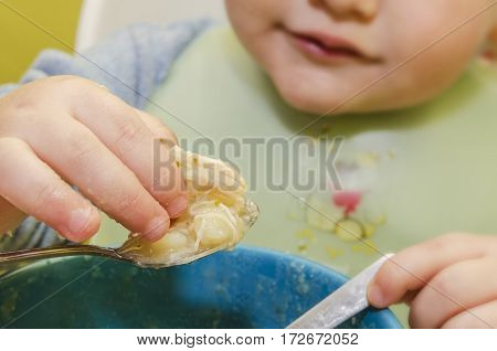 baby eats with a spoon soup yourself