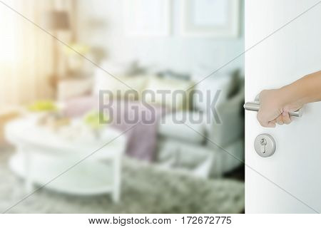 Man Hand Opening White Door To Living Room Interior With Set Of Elegance Sofa