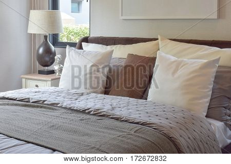 Modern Bedroom Interior With White And Brown Pillow On Bed And Decorative Table Lamp