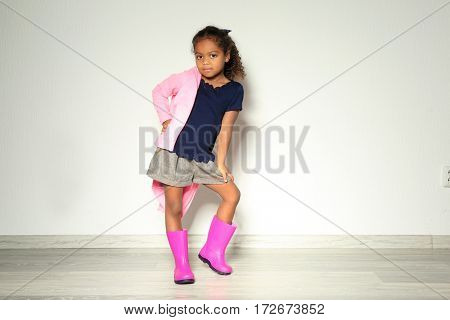 Cute little African American girl in rubber boots against light wall. Fashion concept