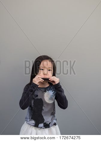Little Asian Child Play The Harmonica, Gray Background