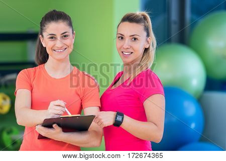 Two young woman enjoying their exercise routine at the gym laughing and smiling as they watch clipboard