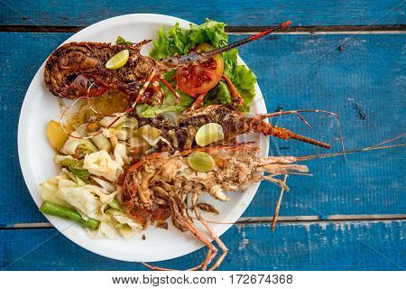 Tasty lobsters and jumbo prawns prepared with garlic and lime on tropical background