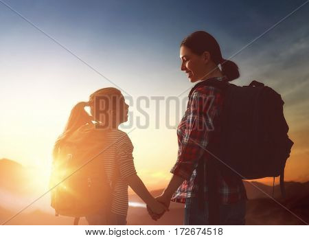 Two travelers at sunset. Mother and child daughter girl are having fun and enjoying journey.