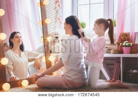 Happy loving family. Cute little girl is combing her mother's hair sitting near mirror in the children room.