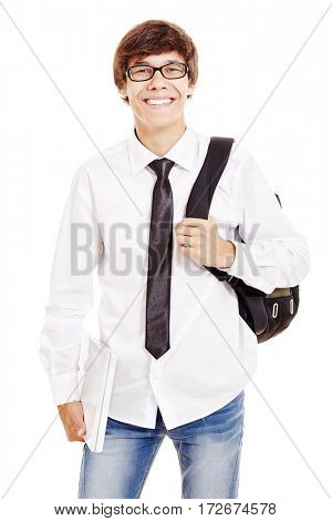 Portrait of young latin man with backpack wearing glasses, blue jeans, white shirt and black tie, holding laptop in his hand and smiling isolated on white background - students and education concept