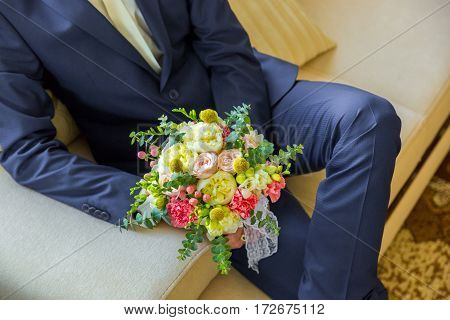 Groom holding a wedding bouquet. The groom in a blue suit