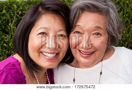 Smiling mature Asian mother and her adult daughter.