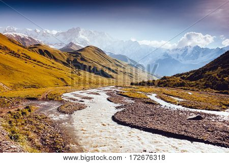 Rapid river at the foot of the glacier Shkhara. Picturesque and gorgeous scene. Location place Svaneti, Mestia, Georgia, Europe. High Caucasus ridge. Vintage effect. Instagram filtered. Beauty world.